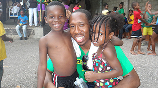 Boston College student with two Jamaican young students