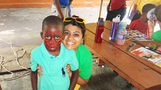Boston College student with young Jamaica student with spiderman face paint