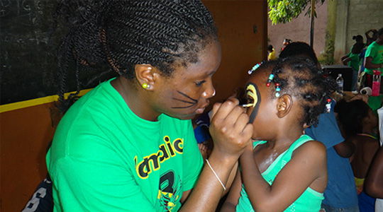 Boston College student painting face of young Jamaican girl