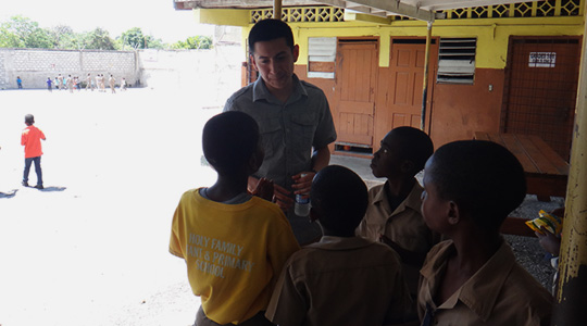 Boston College student talking to a group of young Jamaican students