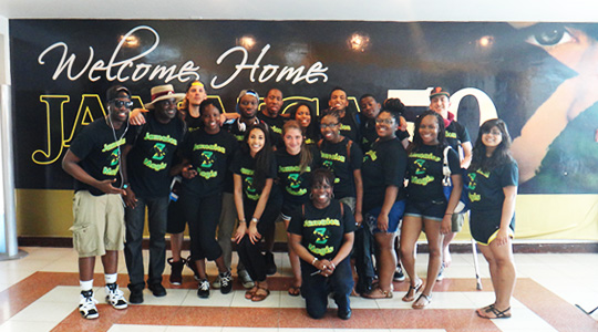 "Group photo of Boston College students in front of sign ""Welcome Home Jamaica"""