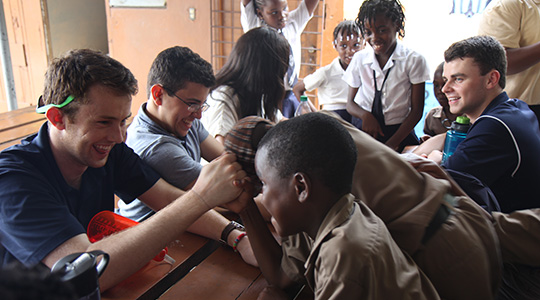 BC students arm-wrestling with Jamaican students