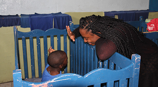 BC student giving a high-five to a Jamaican child in crib