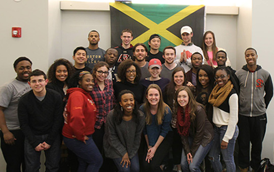 group photo of Boston College students in front of Jamaican flag