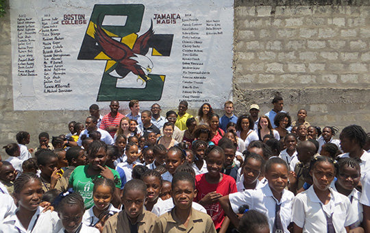 Jamaican school children in front of wall with names of Boston College students from Jamaica Magis