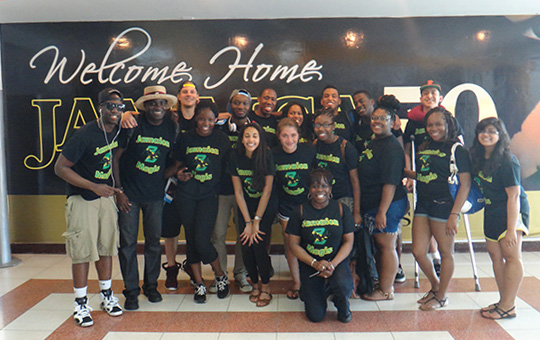 "Group of Boston College students in front of a sign that says, ""Welcome Home Jamaica"""