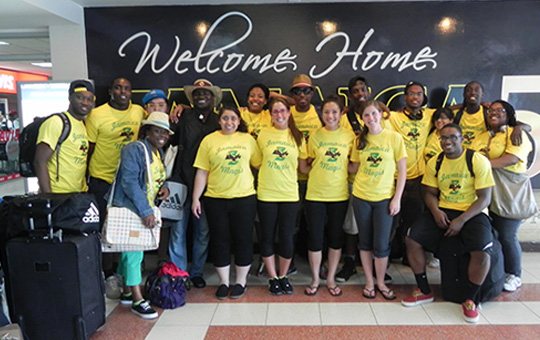 "Group of Boston College students in yellow Jamaica Magis shirts in front of ""Welcome Home Jamaica"" sign"