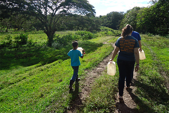 Arrupe student walking with young boy on a path, both holding water jugs.