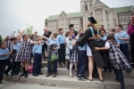 school children hugging graduate